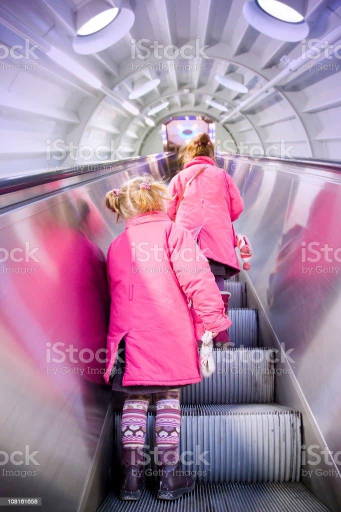 Two Little Girls Riding Escalator royalty-free stock photo