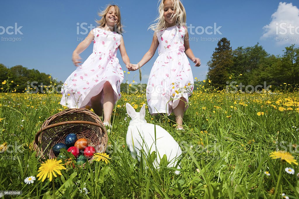 Two little girls running to a basket with eggs and bunny stock photo
