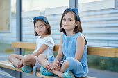 two little girls sit on the bench waiting for the bus in summer