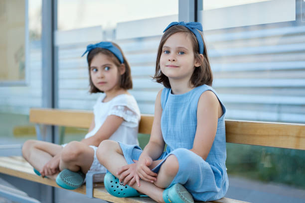 two little girls sit on the bench waiting for the bus