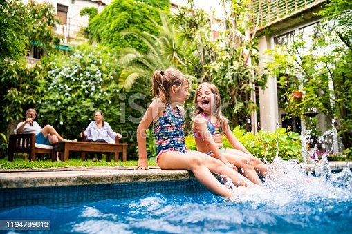 Two little girls sitting at poolside and splashing water with legs.