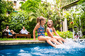 istock Two little girls sitting at poolside and splashing water with legs 1194789613