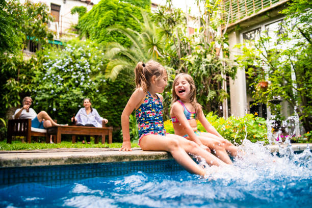 Two little girls sitting at poolside and splashing water with legs Two little girls sitting at poolside and splashing water with legs. swimming pool stock pictures, royalty-free photos & images