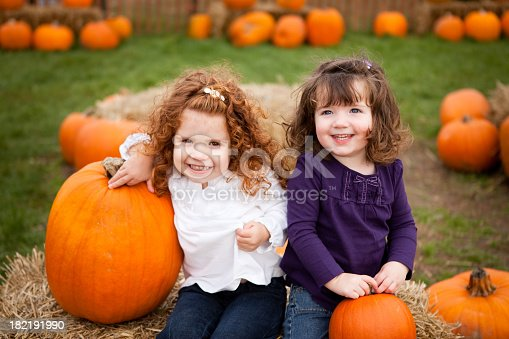 Color photo of two cute little girls smiling in a pumpkin patch.