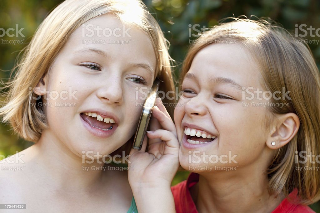Two little girls smiling talking on mobile cell phone outdoors royalty-free stock photo
