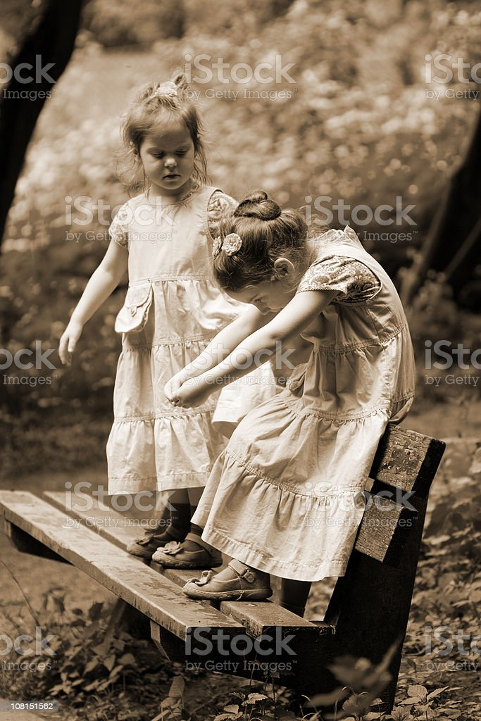Two Little Girls Standing on Park Bench, Sepia Toned  Auto Post Production Filter Stock Photo