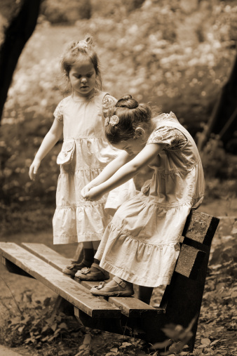 Two Little Girls Standing On Park Bench Sepia Toned Stock Photo - Download Image Now