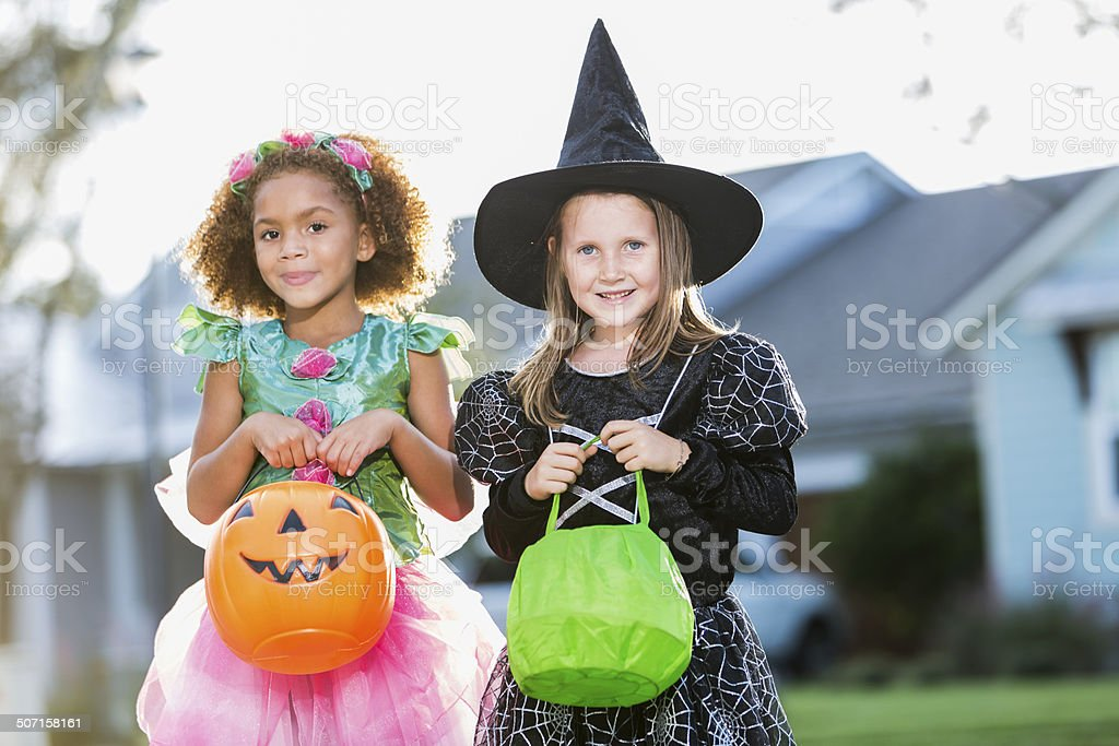 Two little girls trick or treating on Halloween stock photo