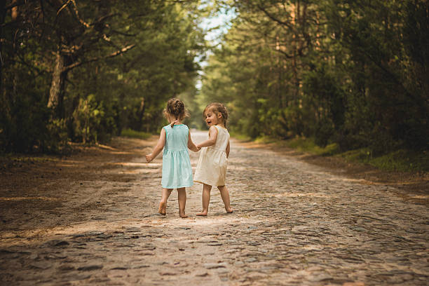two little girls walking along a forest road