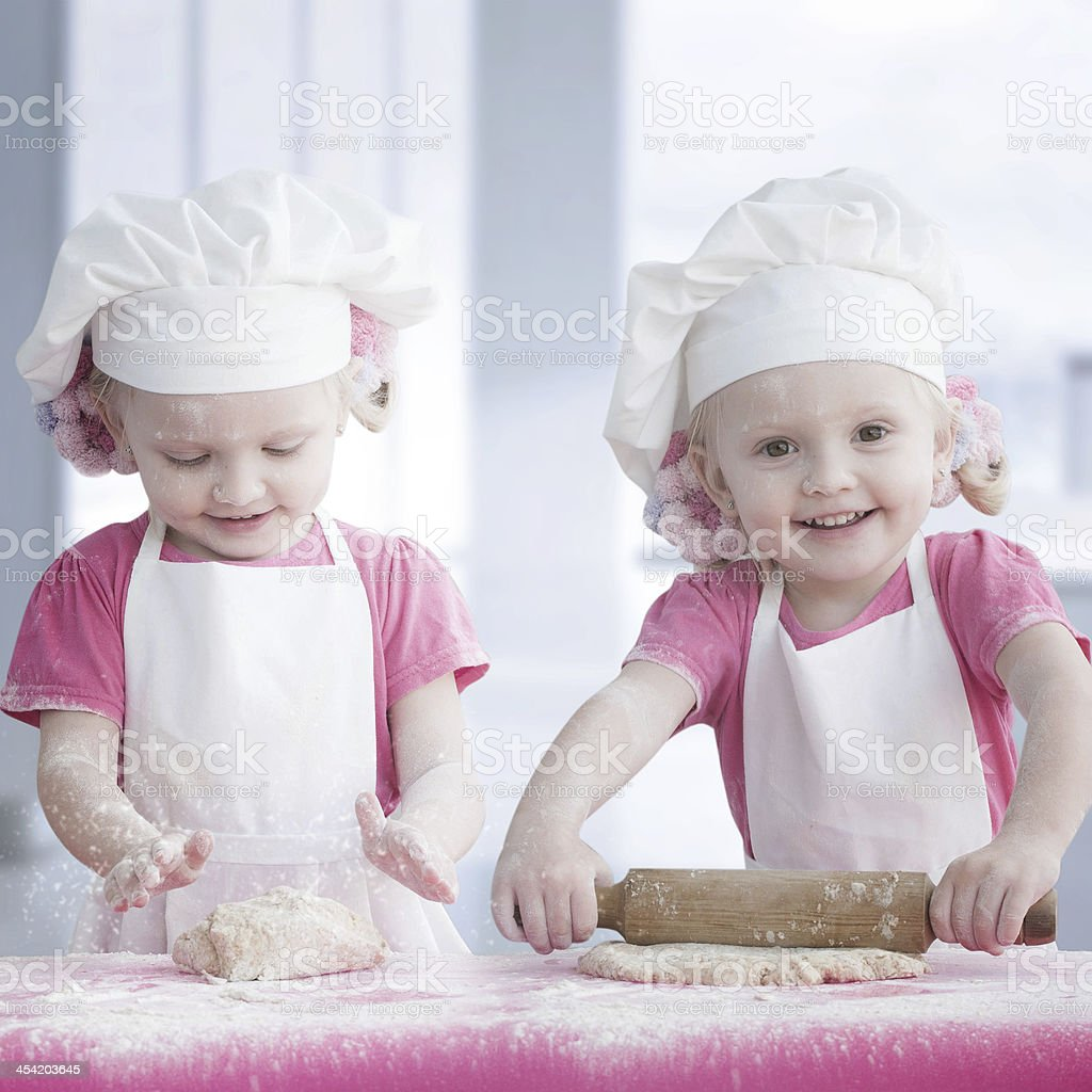 Two little girls wearing white aprons and chefs hats baking royalty-free stock photo