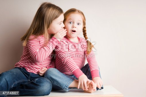 Color photo of a five-year-old girl whispering secrets to her three-year-old sister.
