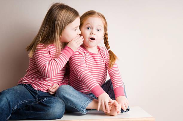 Two Little Girls Whispering Surprising Secrets stock photo