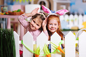 two little girls with rabbit ears hiding behind a white decorative fence and hunting for the Easter bunny. Preparing for the celebration of Easter