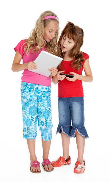 zwei kleine mädchen mit tablet-gerät - denim caprihosen stock-fotos und bilder