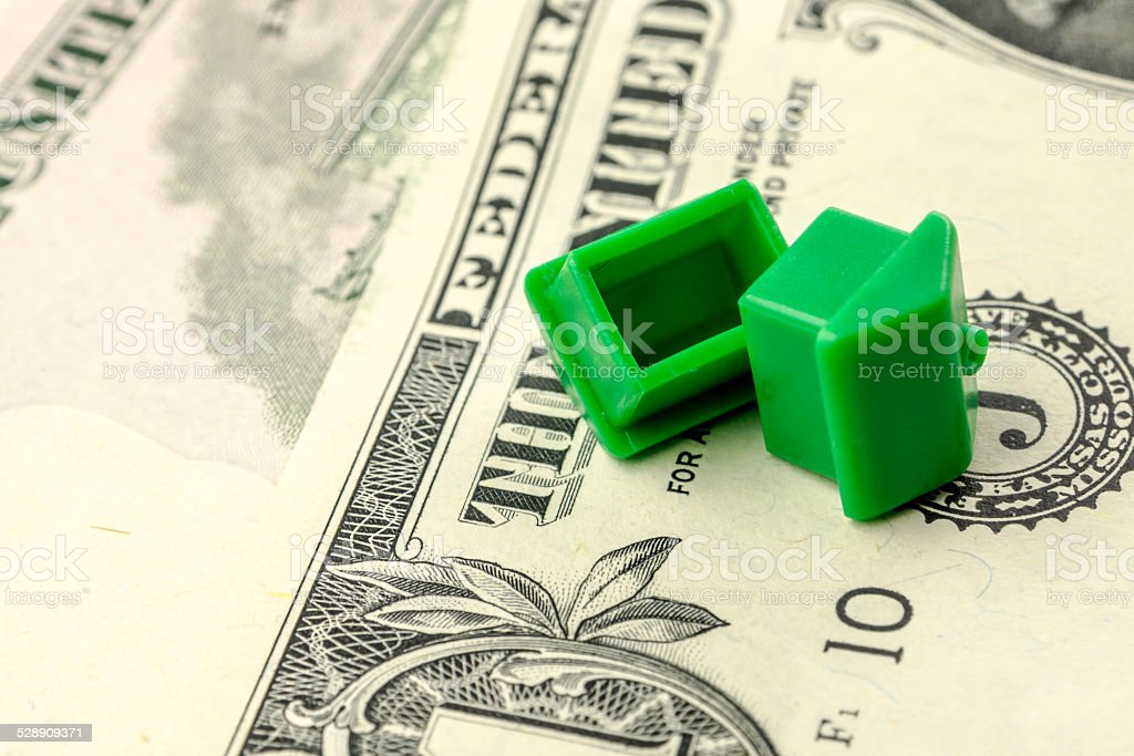 two little green plastic houses are laying on their roof stock photo