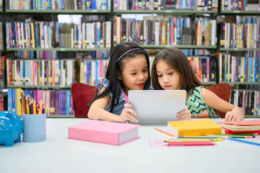 Two little happy cute girls playing on a tablet PC computing device in library at school. Education and self learning wireless technology concept. People lifestyles and friendship. Preschool children