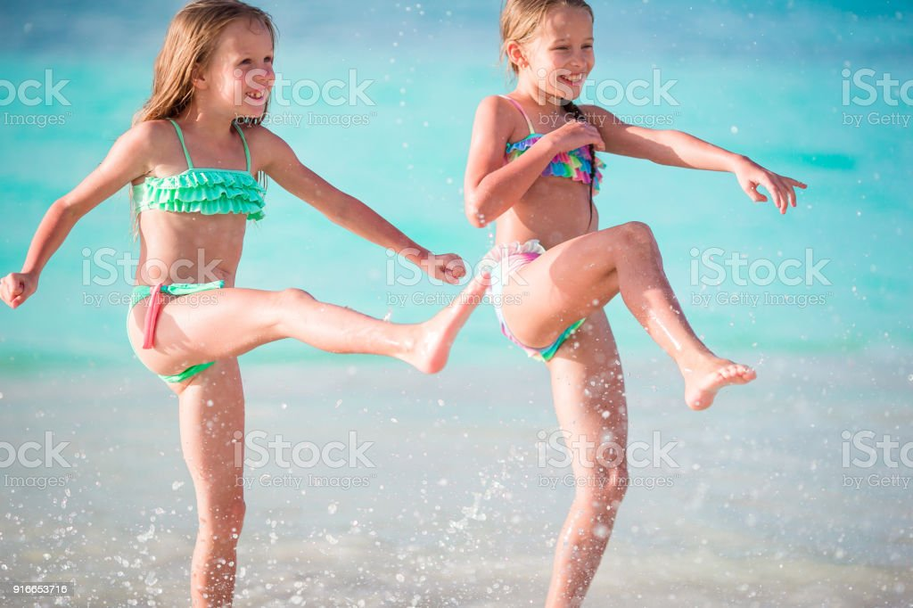 a690d3cdd93e5 Two little happy girls have a lot of fun at tropical beach playing together  at shallow water. Kids splashing. - Stock image .