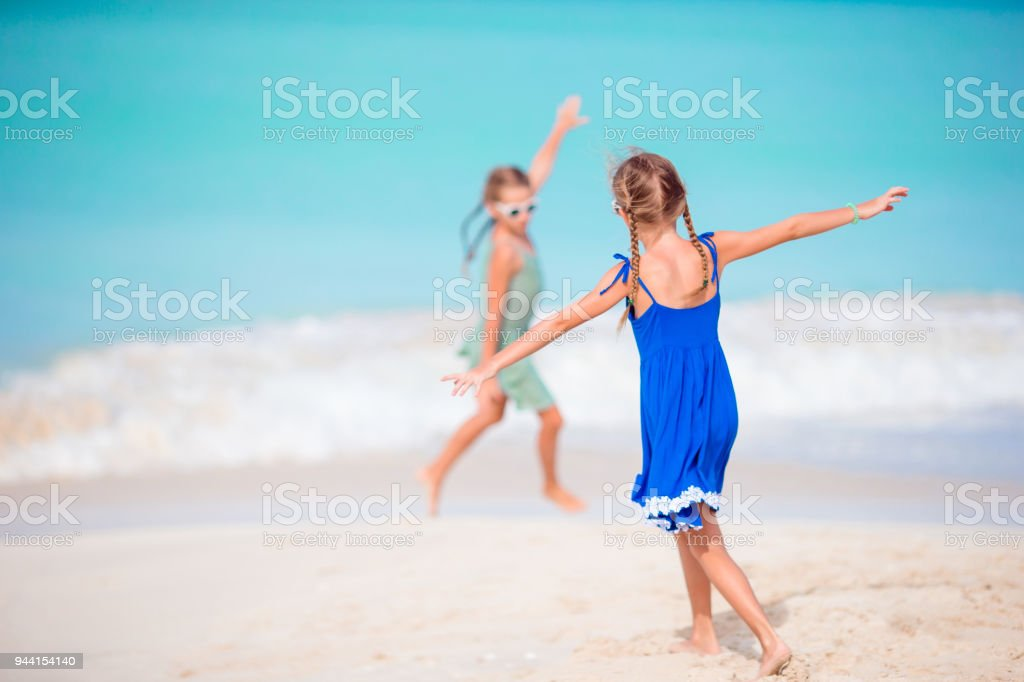 11ec78ca7bd13 Two little happy girls have a lot of fun at tropical beach playing together  - Stock image .