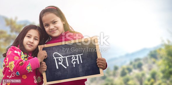 Adorable little 6-8 years old and 8-10 years old Indian/Asian girls smiling, holding education (Shiksha) chalkboard.