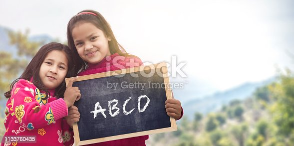 Adorable little 6-8 years old and 8-10 years old Indian/Asian girls smiling, holding abcd chalkboard.