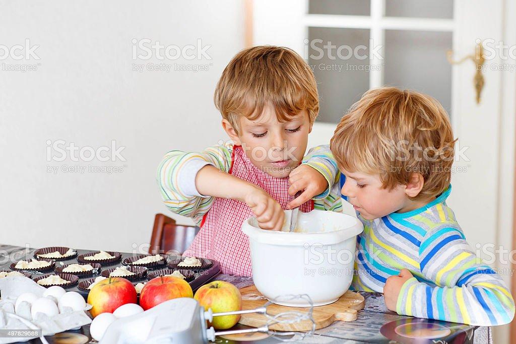 Two little kid boys baking apple cake indoors stock photo