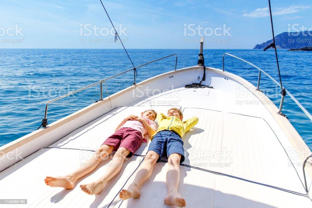 Two little kid boys, best friends enjoying sailing boat trip. Family...