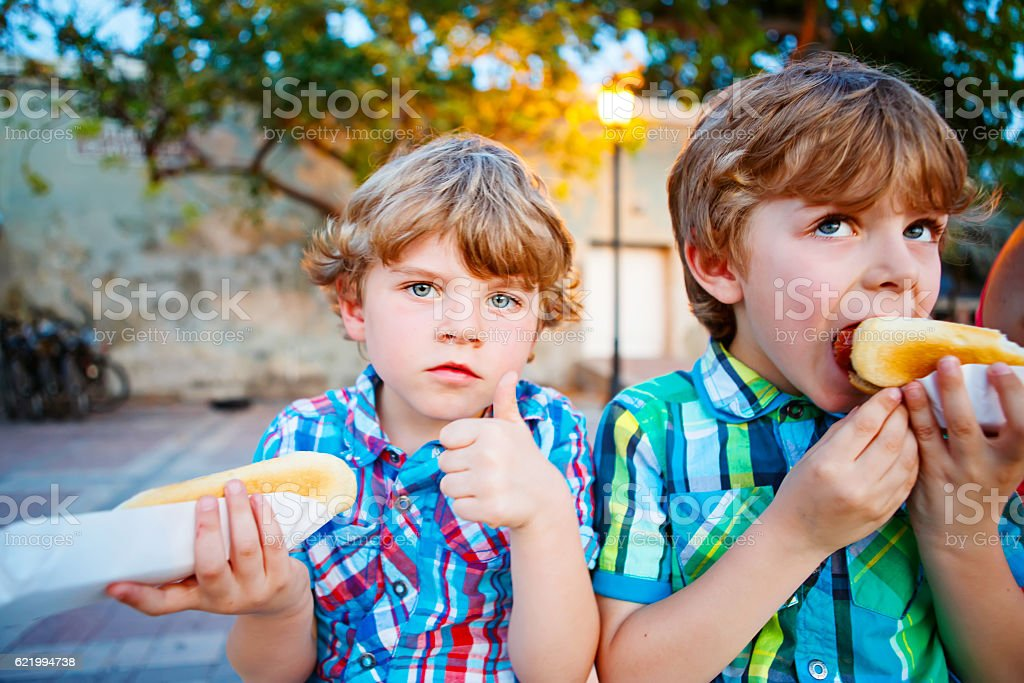 Two little kid boys eating hot dogs outdoors stock photo