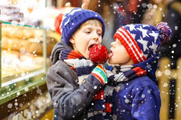 zwei jungen kind zucker apfel süßigkeiten essen stehen auf dem weihnachtsmarkt - vorschuldekorationen stock-fotos und bilder