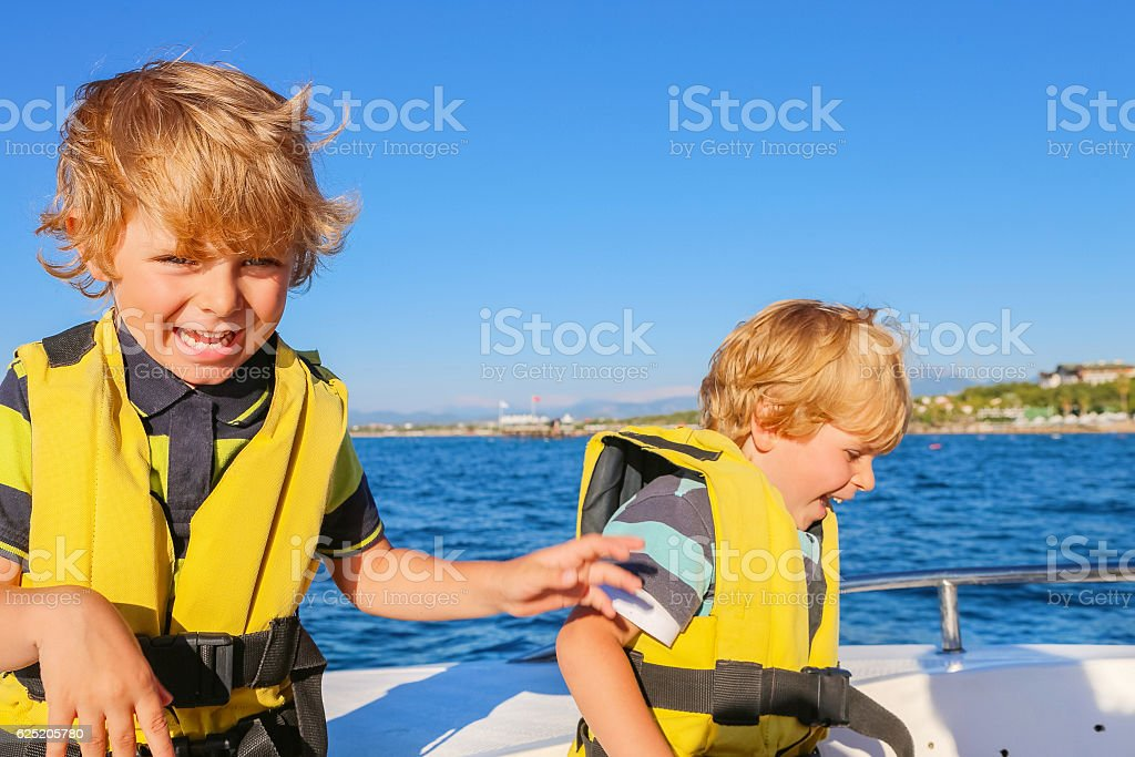 two little kid boys enjoying sailing boat trip stock photo