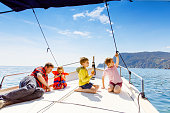 Two little kid boys, father and toddler girl enjoying sailing boat trip. Family vacations on ocean or sea on sunny day. Children smiling. Brothers and sister, siblings and dad having fun on yacht