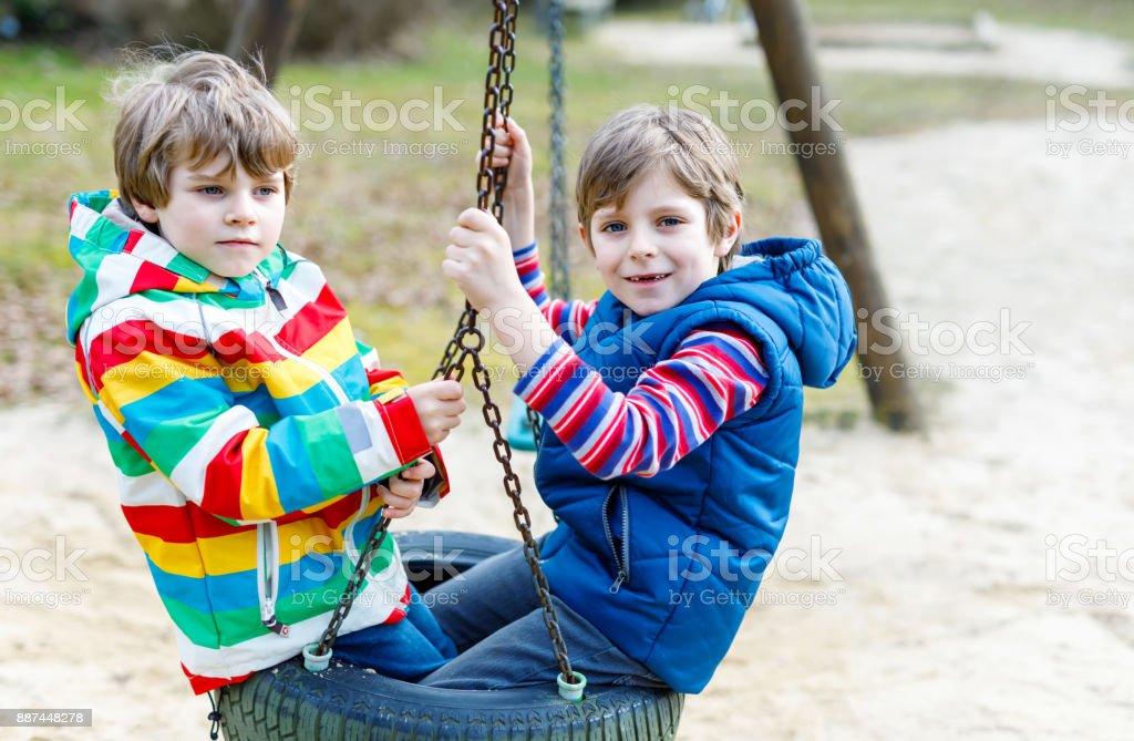 Two little kid boys having fun with chain swing on outdoor playground stock photo