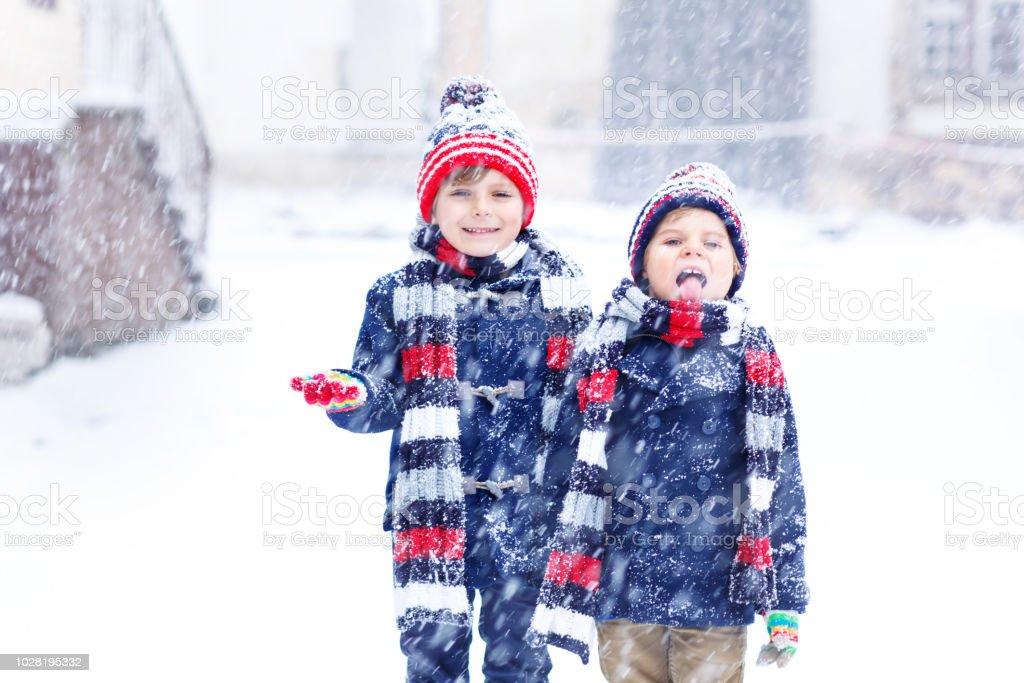 Zwei Kinder wenig Jungs in bunte Mode Kleidung spielen im Freien bei starkem Schneefall. Aktive Freizeitgestaltung mit Kindern im Winter an kalten Tagen. Glücklich Geschwister und Zwillinge, die Spaß mit ersten Schnee – Foto