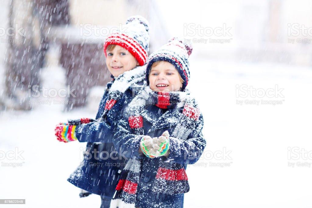 Zwei Kinder wenig Jungs in bunte Mode Kleidung spielen im Freien bei starkem Schneefall. – Foto