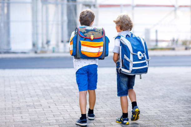 two little kid boys with backpack or satchel. schoolkids on the way to school. healthy adorable children, brothers and best friends outdoors on the street leaving home. back to school. happy siblings. - cartella scolastica foto e immagini stock