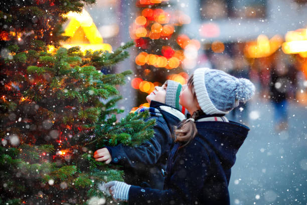 Two little kids, boy and girl having fun on traditional Christmas market during strong snowfall. Happy children enjoying traditional family market in Germany. Twins standing by illuminated xmas tree. stock photo
