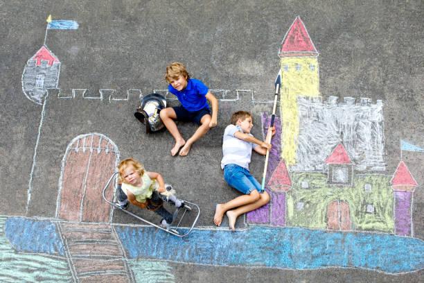 zwei kinder kleine, jungen und niedlichen kleinkind mädchen zeichnung ritterburg mit bunter kreide auf asphalt. glücklich geschwister und freunde, die spaß mit dem erstellen von kreide bild und malerei - sommerfest kindergarten stock-fotos und bilder