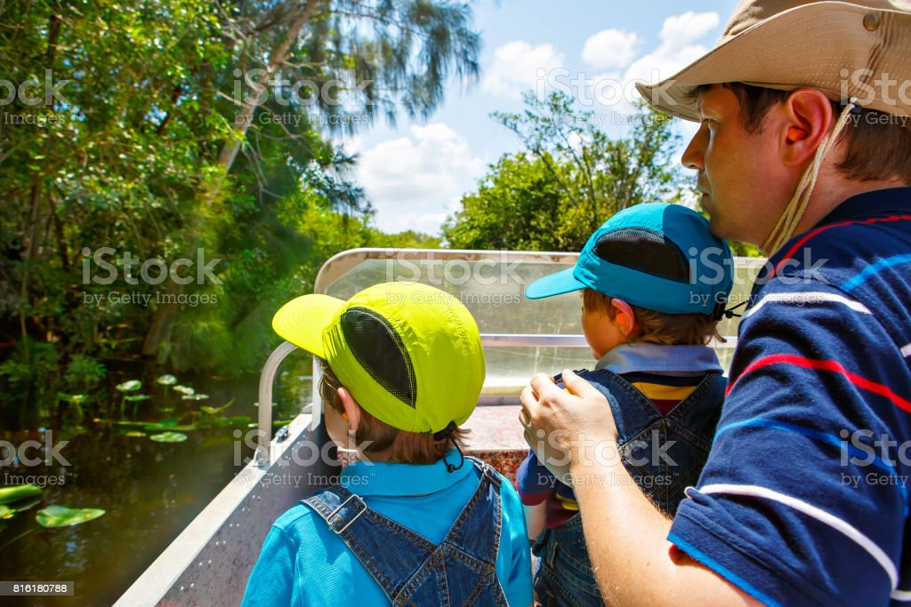 Two little kids boys and father making air boat tour in Everglades Park stock photo