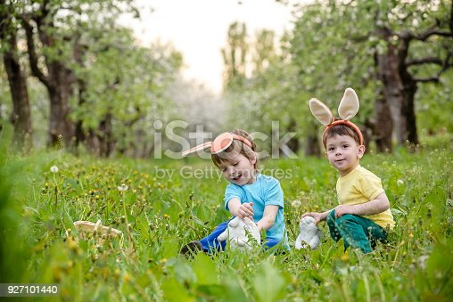 Two little kids boys and friends in Easter bunny ears during traditional egg hunt in spring garden, outdoors. Siblings having fun with finding colorful eggs. Old christian and catholoc tradition.