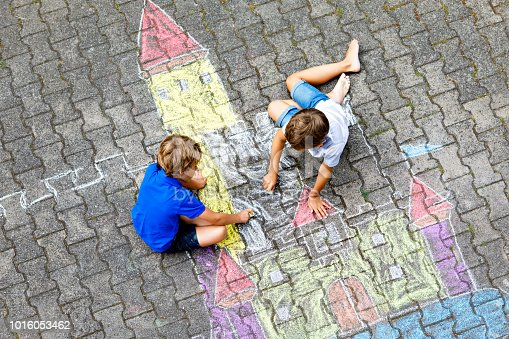 Two little kids boys drawing knight castle with colorful chalks on asphalt. Happy siblings and friends having fun with creating chalk picture and painting. Creative leisure for children in summer