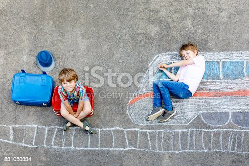istock Two little kids boys having fun with train picture drawing with colorful chalks on ground 831050334