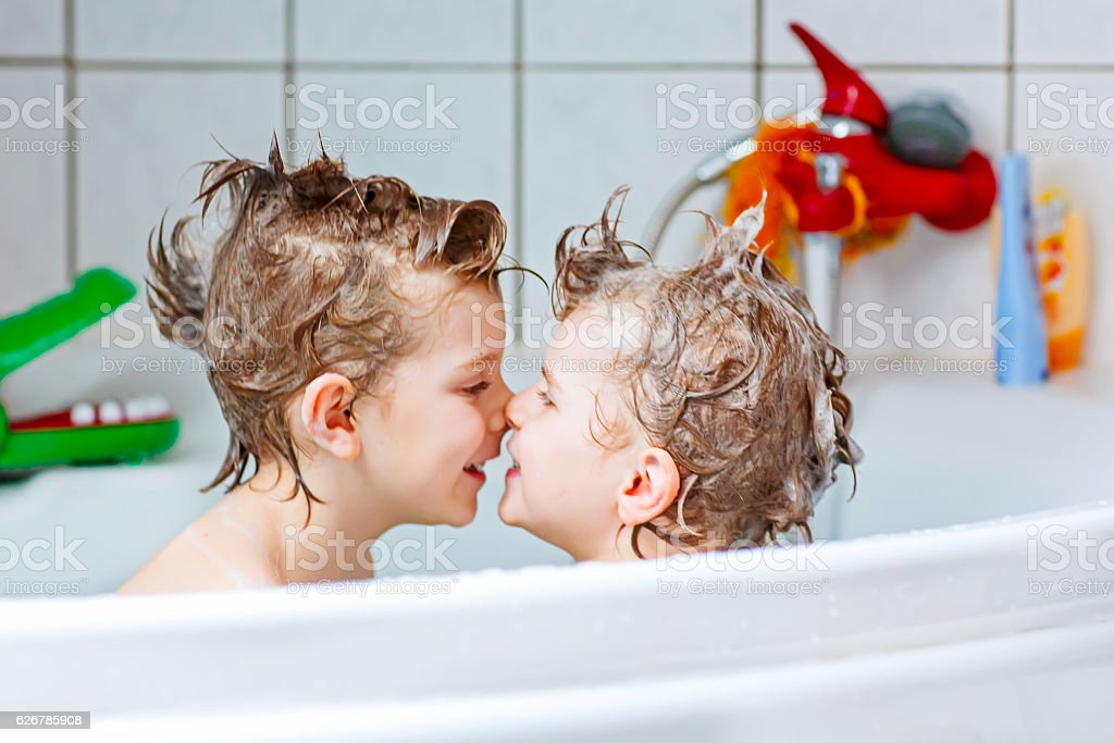 Two little kids boys playing together in bathtub – Foto