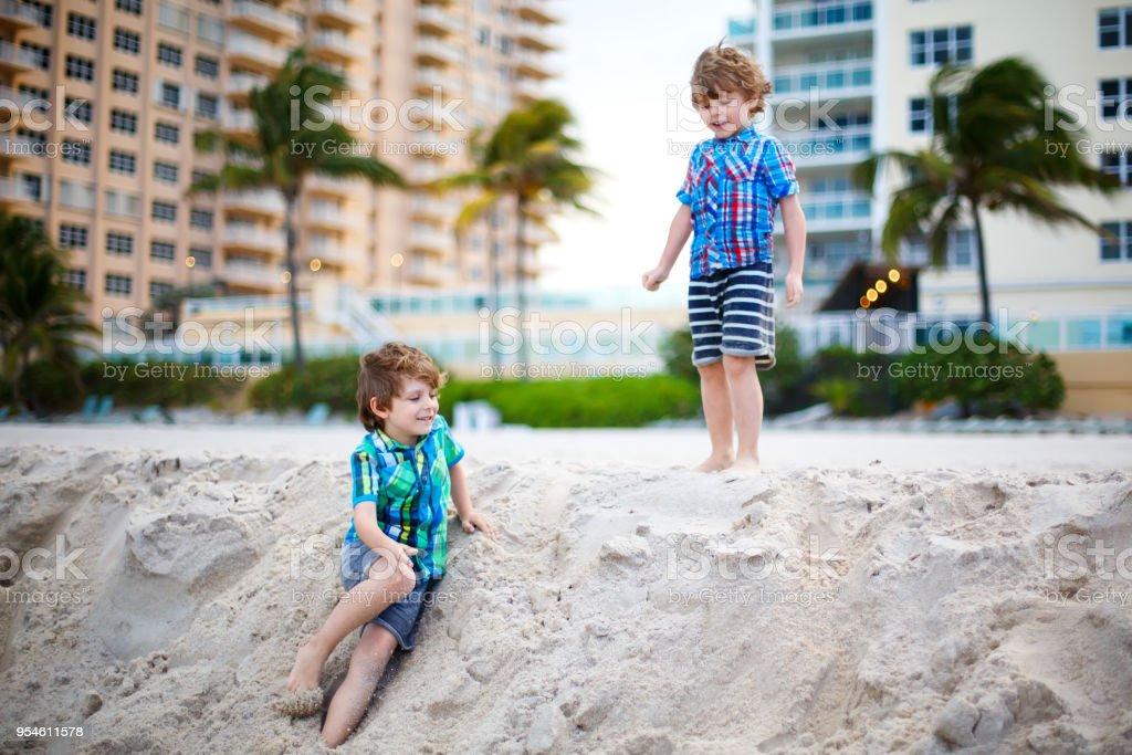 Two little kids boys running on the beach of ocean stock photo