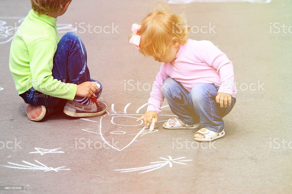 little boy and toddler girl drawing rocket on asphalt, kids outdoor...