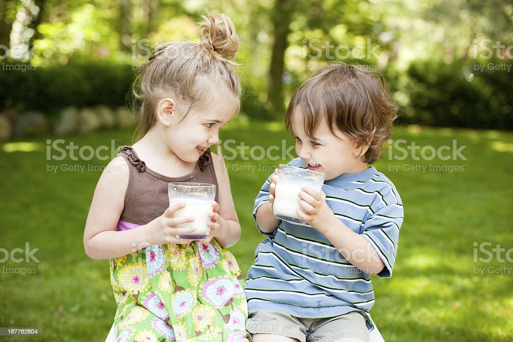 Two Little Kids Drinking Milk While Outdoors stock photo