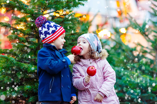 Two little kids eating crystalized apple on Christmas market