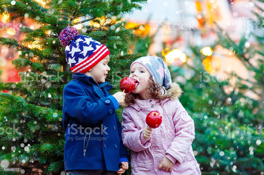 Two little kids eating crystalized apple on Christmas market stock photo