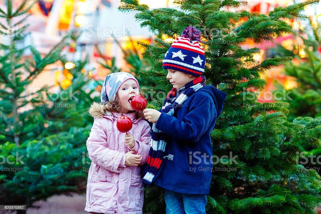 Dois pequenos crianças a comer maçã crystalized no mercado de Natal foto de stock royalty-free