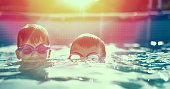 Two little kids in goggles swimming in pool at vintage sunset