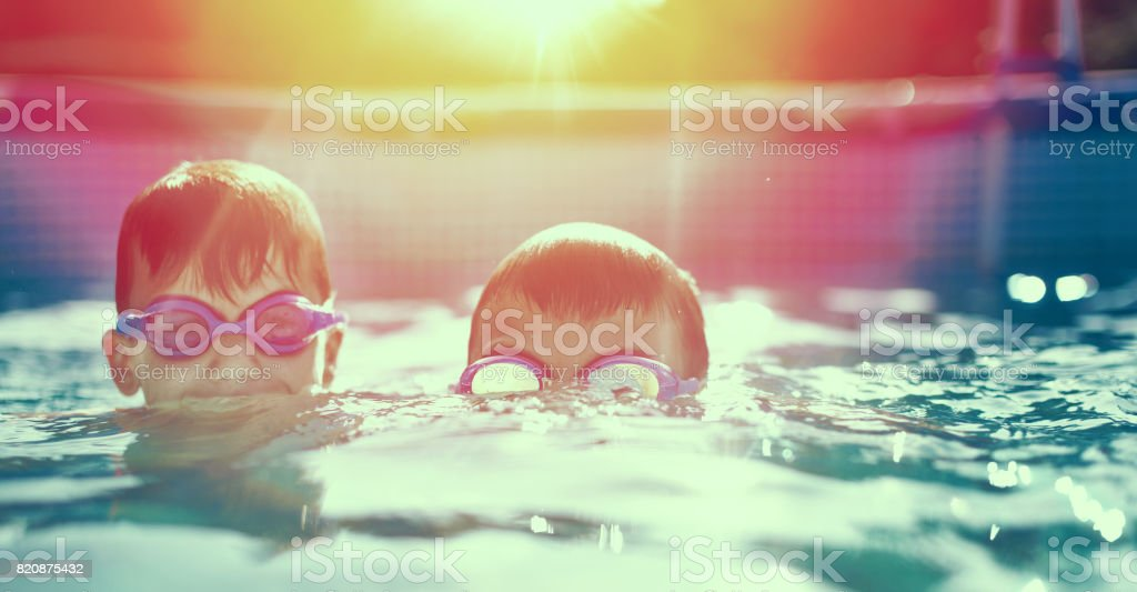 Two little kids in goggles swimming in pool at sunset stock photo