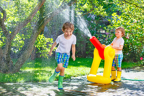 two little kids playing with sprinkler and water in summer - hinterhofhaltung stock-fotos und bilder